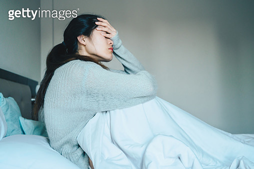 Portrait of sickness woman sitting alone on the bed in the bedroom, self isolation herself during coronavirus pandemic outbreak. - gettyimageskorea