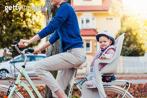 Mother and daughter riding bicycle, baby wearing helmet sitting in children's seat - gettyimageskorea