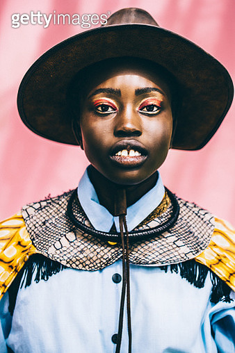 Portrait of a beautiful African girl against a vibrant pink background. - gettyimageskorea