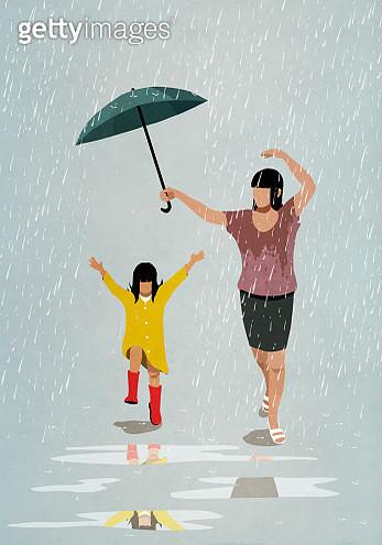 Carefree mother and daughter dancing in rain - gettyimageskorea