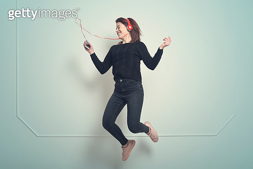 Cheerful Young Woman Jumping While Listening Music Against blue Background - gettyimageskorea