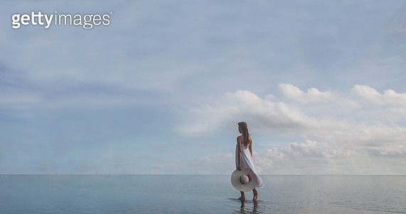 Young woman wearing white dress and holding a sun hat walking on the edge of an infinity pool on the ocean - gettyimageskorea