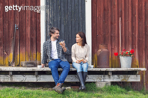 Couple having breakfast while sitting outside barn at farm - gettyimageskorea