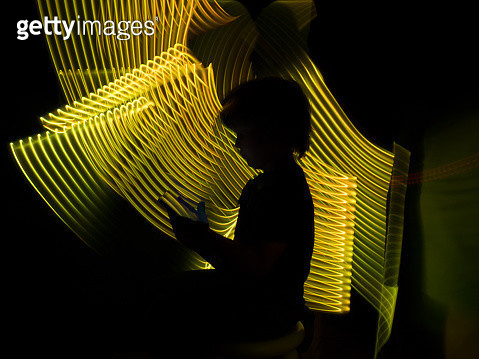 Child shape looking a tablet in a futuristic yellow virtual environment. - gettyimageskorea