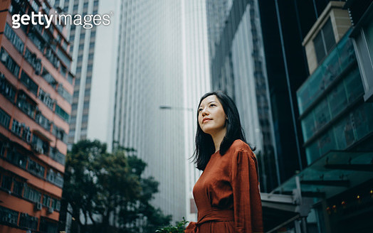 Low angle portrait of confidence young woman standing against highrise city buildings in city - gettyimageskorea