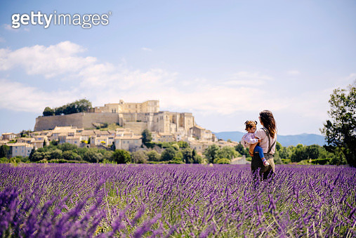 France, Grignan, mother standing in lavender field with little daughter on her arms looking at village - gettyimageskorea