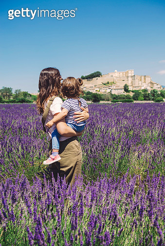 France, Grignan, back view of mother and little daughter standing together in lavender field looking at village - gettyimageskorea