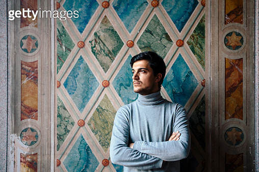 Portrait of a young man looking away arms crossed against the wall - gettyimageskorea