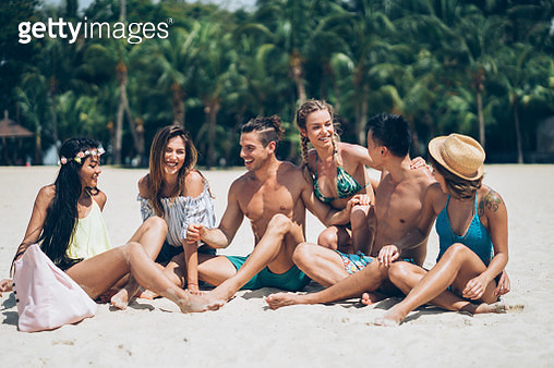 Group of friends on a summer vacation sitting on the sand - gettyimageskorea