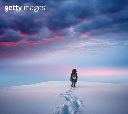 Woman hiking to the top of a snowcapped mountain peak at sunset. - gettyimageskorea