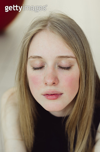 Close-up of young caucasian woman with eyes closed. - gettyimageskorea
