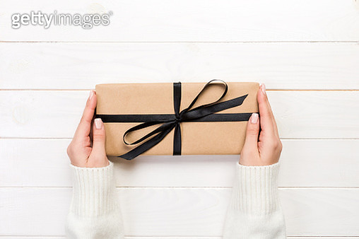 Cropped Hands Of Woman Holding Wrapped Gift Box On Table - gettyimageskorea