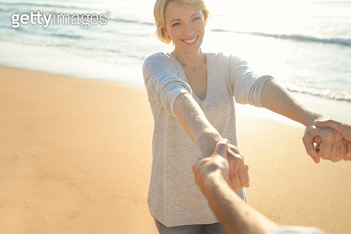 Beautiful mature woman dancing and playing on the beach. - gettyimageskorea