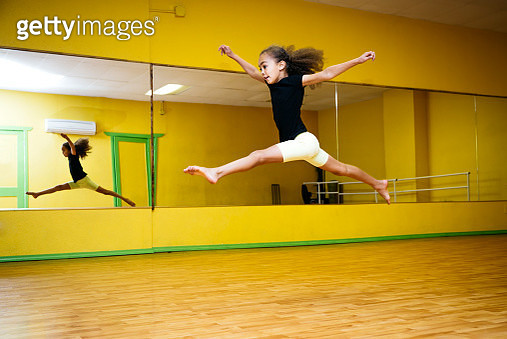 Mixed race girl leaping in ballet studio - gettyimageskorea