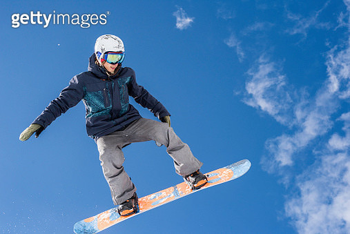 Snowboarder in mid-air on blue sky background - gettyimageskorea