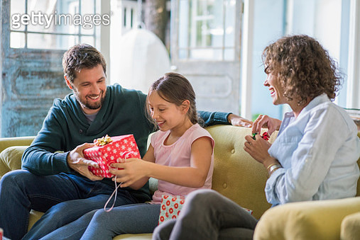 Happy parents giving present to daughter at home - gettyimageskorea