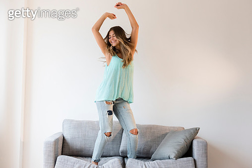 Mixed race woman jumping on sofa - gettyimageskorea