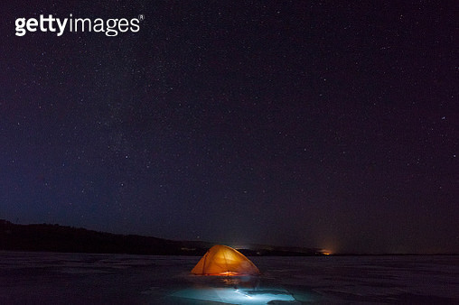 Russia, Amur Oblast, illuminated tent on frozen Zeya River at night under starry sky - gettyimageskorea