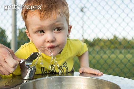 Cute Redhead Boy Drinking Water From Water Fountain - gettyimageskorea