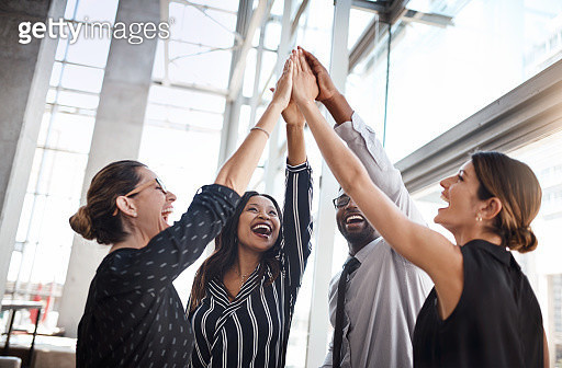 Shot of a group of professional businesspeople high fiving in the office - gettyimageskorea