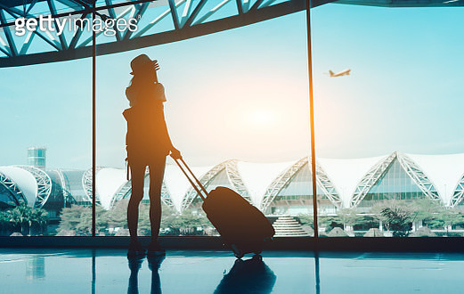 Silhouette Woman With Luggage Standing In Airport - gettyimageskorea
