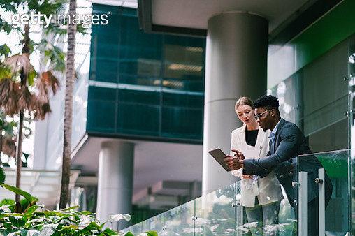 Businessman and Businesswoman Having Conversation in Front of Their Office - gettyimageskorea