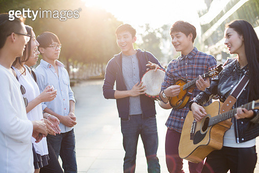 Young adults playing musical equipment on street - gettyimageskorea