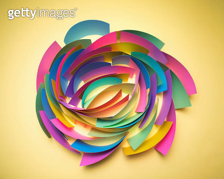 Green, pink, blue, yellow and purple sheets of paper on edge in circular pattern on yellow background - gettyimageskorea