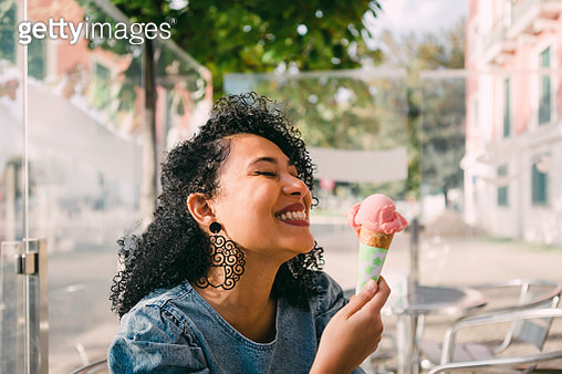 Carefree, excited young woman enjoying pink ice cream cone on sunny cafe patio - gettyimageskorea