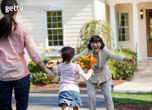Family welcoming woman with flowers - gettyimageskorea