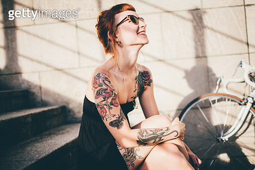Woman smiling in sunshine with ring on necklace - gettyimageskorea