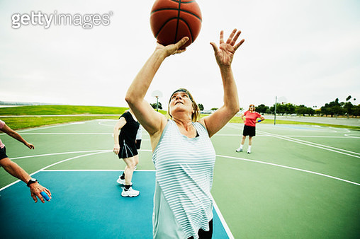 Mature woman shooting layup during basketball game on outdoor court - gettyimageskorea