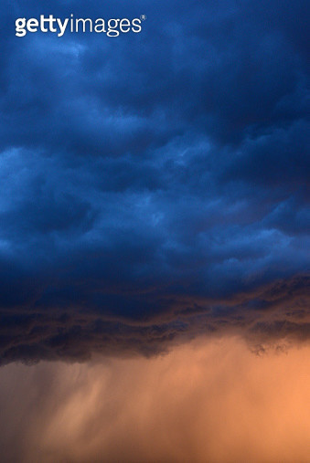 Menacing blue and purple storm clouds over cream colored sky. - gettyimageskorea