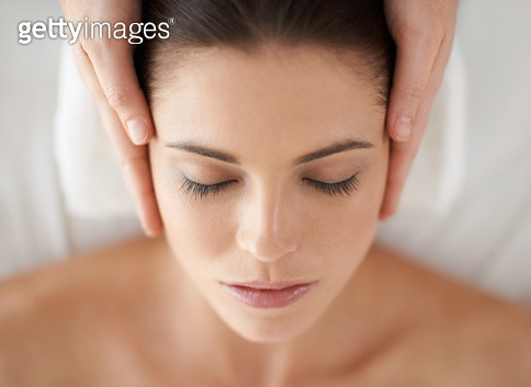 A young woman receiving a face massage - gettyimageskorea