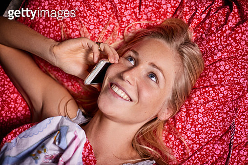 Smiling young woman lying down talking on cell phone - gettyimageskorea