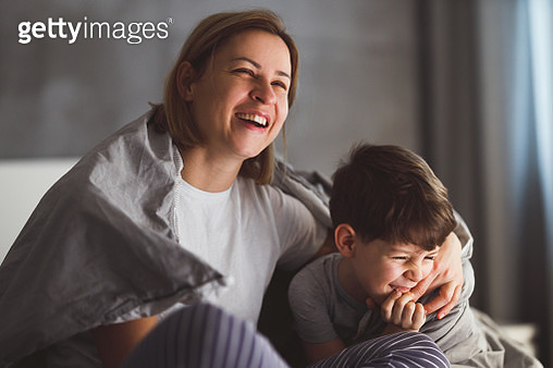 Young mother and her 7 year old son are cuddling in the bed. - gettyimageskorea