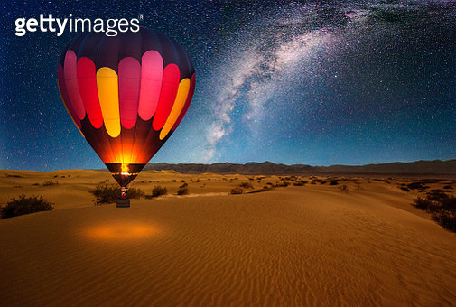 A majestic hot air balloon soars under the stars of the Milky Way, over the desert - Mesquite Dunes of Death Valley National Park. Moonlight provides luminosity showing the patterns and shapes of the desert landscape. - gettyimageskorea