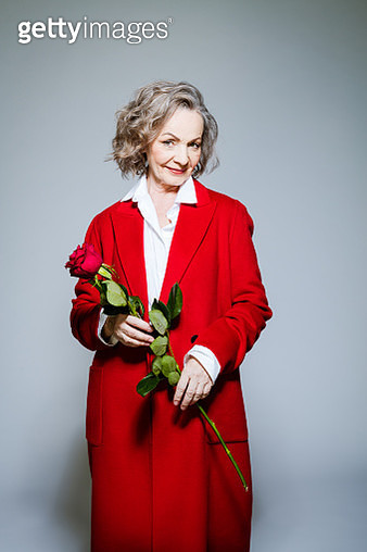 Elderly lady wearing red coat and white shirt standing against grey background, holding red rose in hands and smiling at camera. Studio shot of female designer. - gettyimageskorea