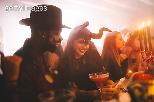 Young multi-ethnic friends in costumes texting at Halloween party - gettyimageskorea