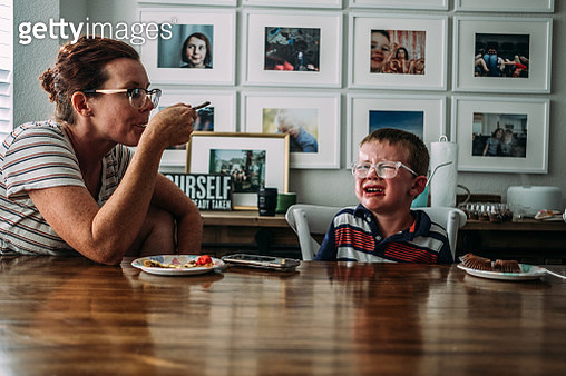 boy having a tantrum while mom takes a bite of cake nearby - gettyimageskorea