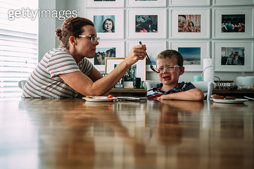 Mom feeding young son a piece of cake at table - gettyimageskorea