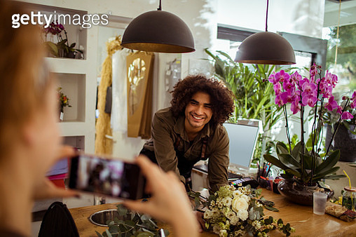 Close up of two colleagues taking pictures while working in a flower shop - gettyimageskorea