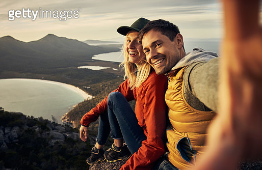 Cropped portrait of an affectionate young couple taking selfies while sitting on a mountain peak - gettyimageskorea