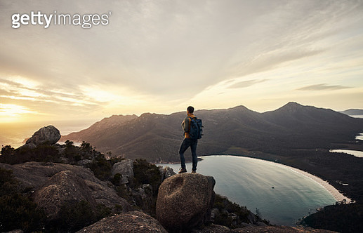 Rearview shot of a young man taking in the view while standing on a mountain peak - gettyimageskorea