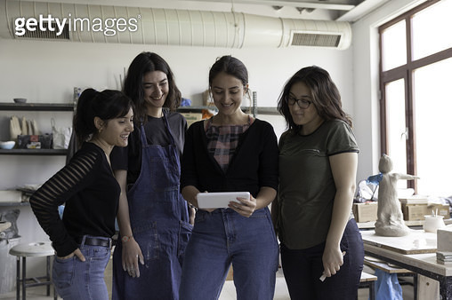 Smiling young woman using tablet in ceramics studio - gettyimageskorea