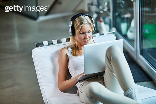 Young woman wearing headphones and using laptop on lounge chair at home - gettyimageskorea