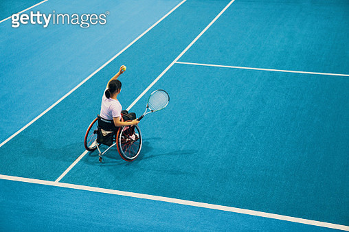 High angle view of a teenage girl playing and practicing wheelchair tennis at an indoor tennis court - gettyimageskorea