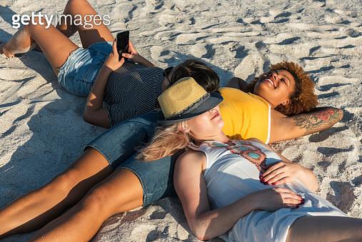 Friends sunbathing at the beach - gettyimageskorea