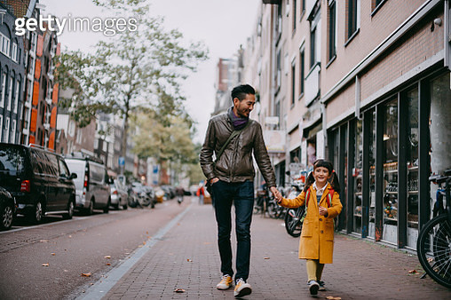 Japanese father and mixed race young girl holding hands and walking on street in Amsterdam, Netherlands - gettyimageskorea