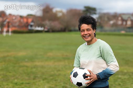 Mature Black Woman Holding a Football - gettyimageskorea